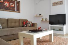 Sala de estar bastante bien amueblada que incluye escritorio y televisión