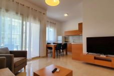 Una hermosa y luminosa sala de estar que incluye cocina y televisión.
