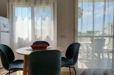 Mesa de pan con 4 sillas azules frente a las ventanas