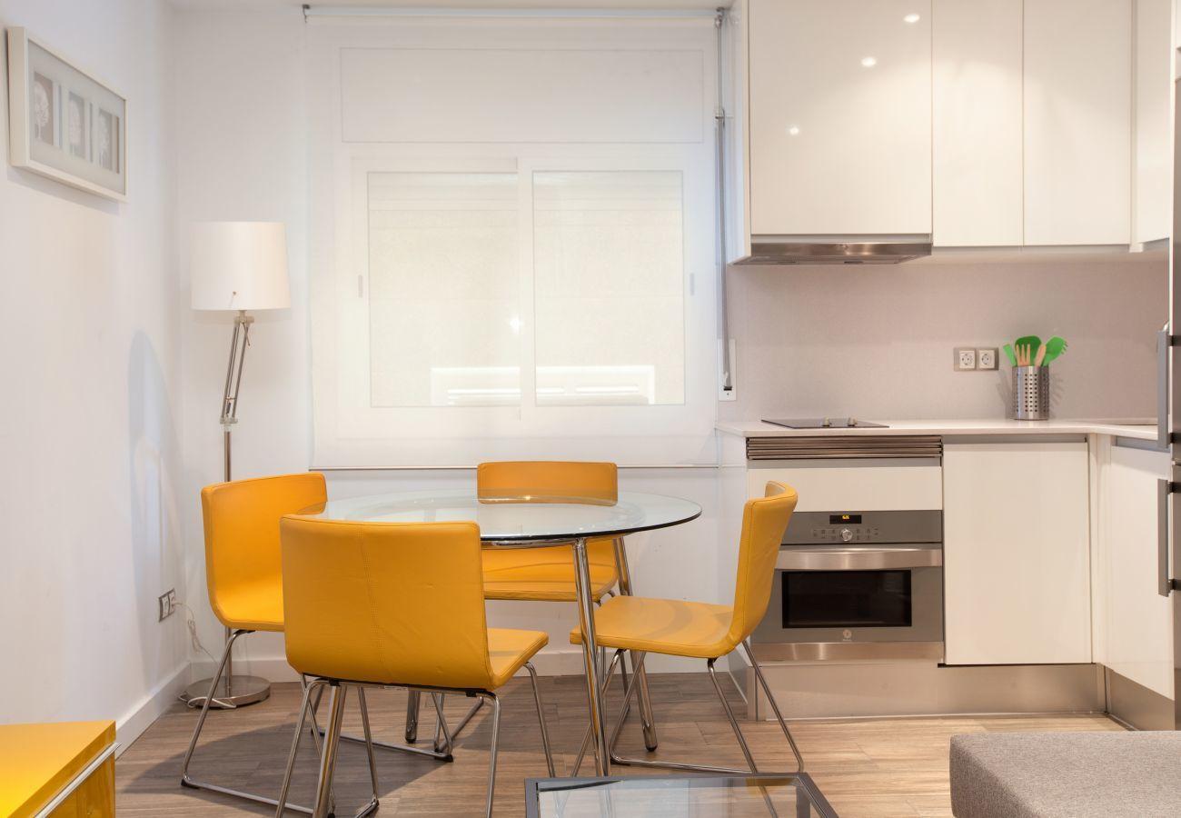 mesa de comedor con sillas y cocina americana en apartamento de 2 dormitorios en Barcelona
