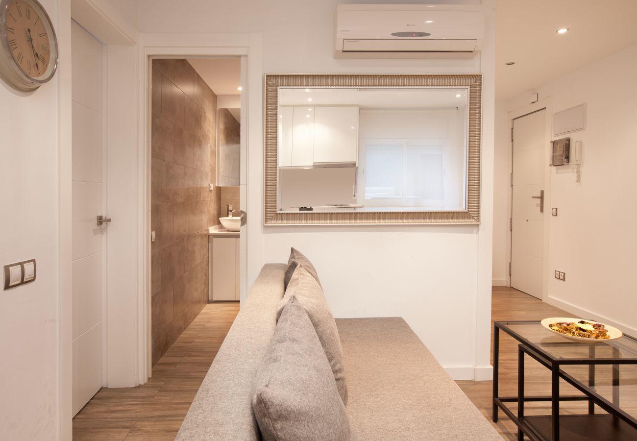 bonito salón con sofa-cama y acceso al baño con ducha en Barcelona cerca de Sagrada Familia