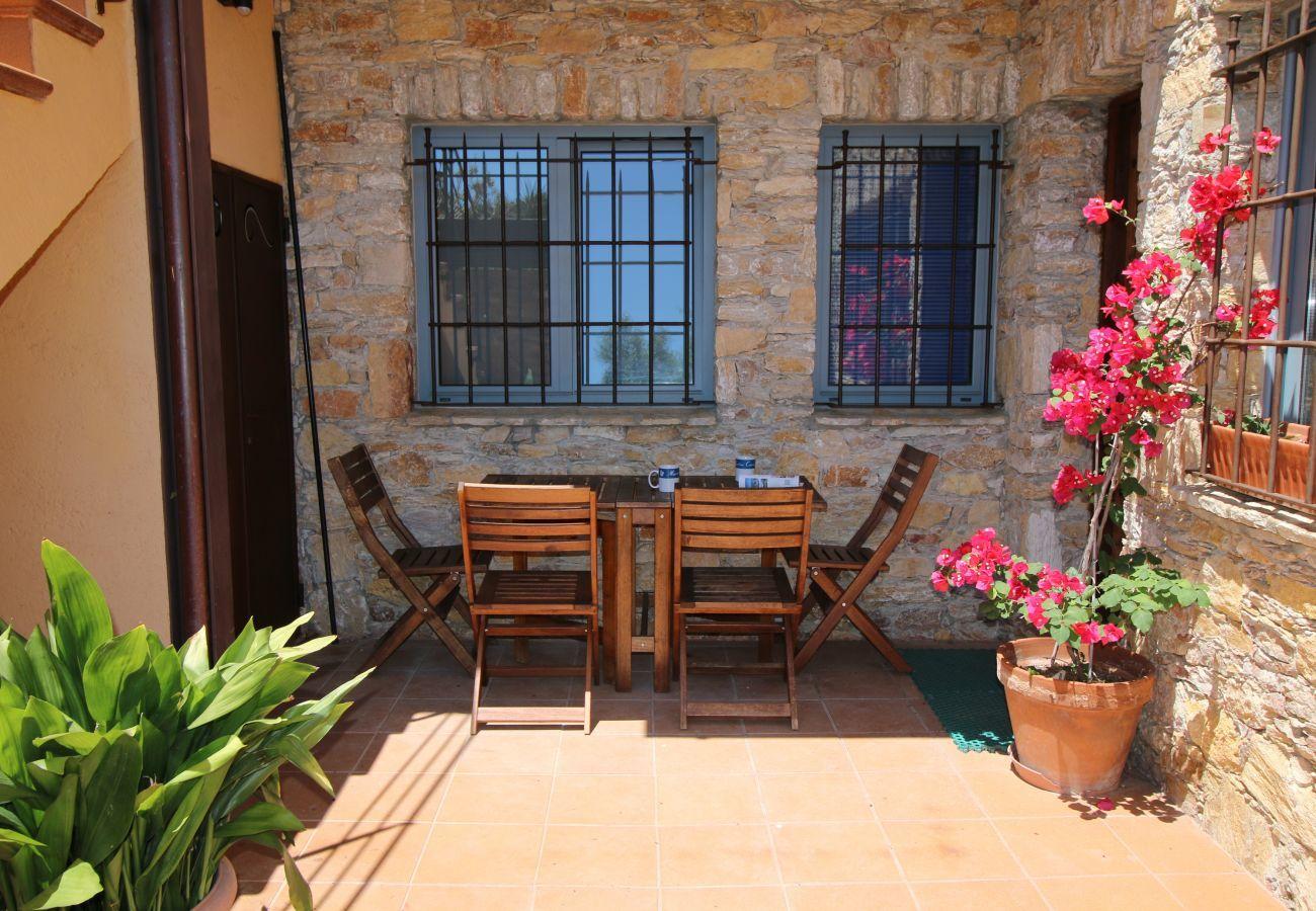 Terraza soleada del apartamento AMETLLER en Begur con mesa, sillas y plantas