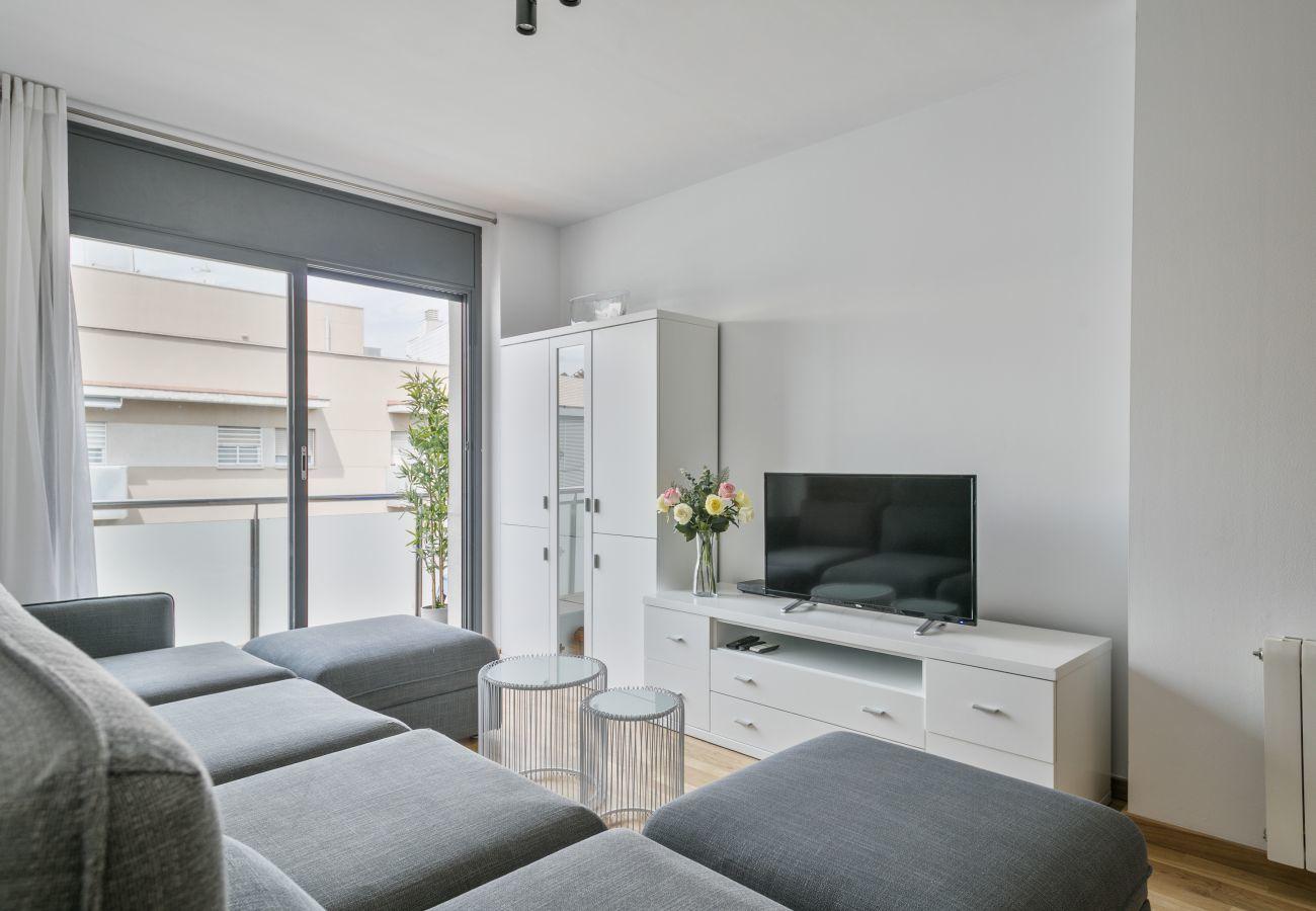luminoso salón con TV y salida al balcón de apartamento de 3 habitaciones