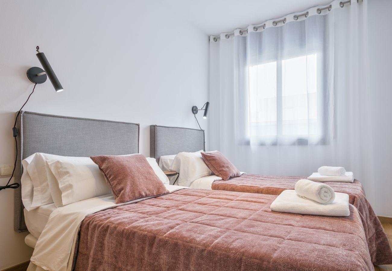 Habitación con dos camas individuales y armario en apartamento de 3 habitaciones y 2 baños