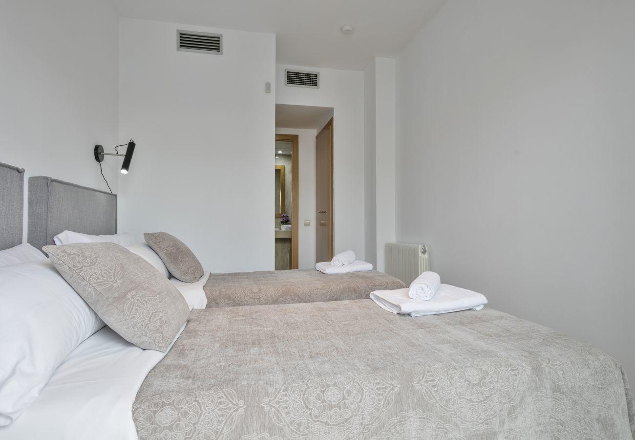dormitorio principal con baño privado con bañera y armarios en apartamento superior en Barcelona
