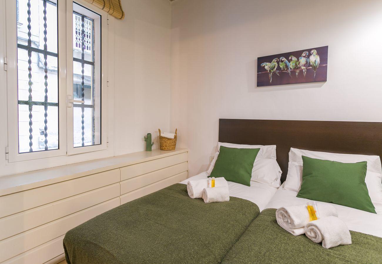 dormitorio con 2 camas individuales, armario y ventana exterior