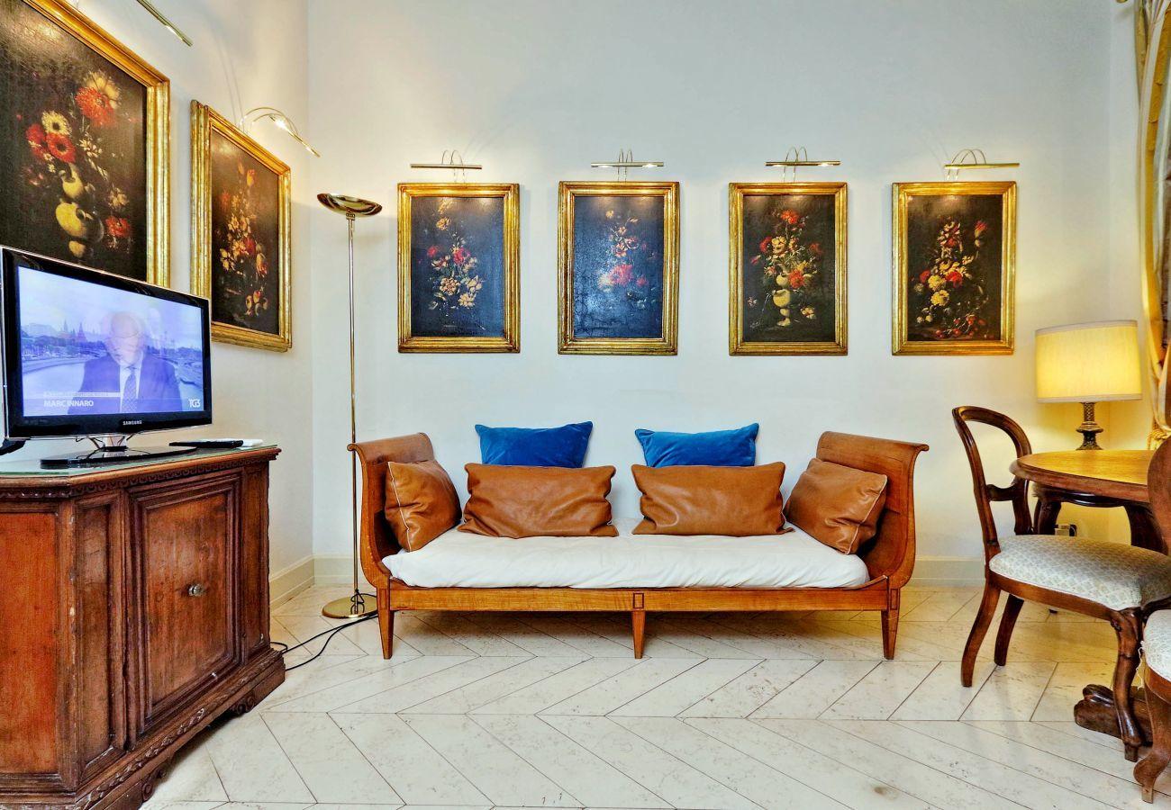BOCCACCIO - sala de estar con muebles clásicos: sofá de dos plazas, mueble de TV con TV, mesa de comedor, sillas, lámpara y cuadros