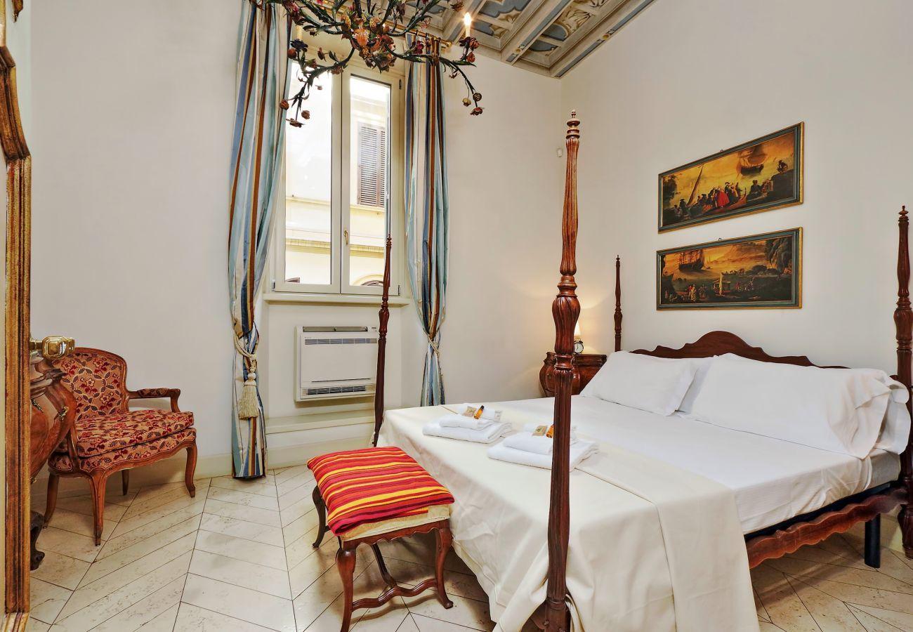 dormitorio con cama doble, mesitas de noche de estilo clásico y banco acolchado a los pies de la cama