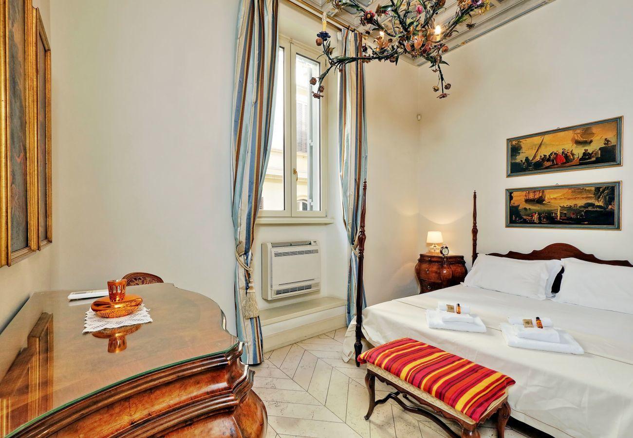 dormitorio con cama de matrimonio, mesitas de noche y tocador de estilo clásico y banco acolchado a los pies de la cama.