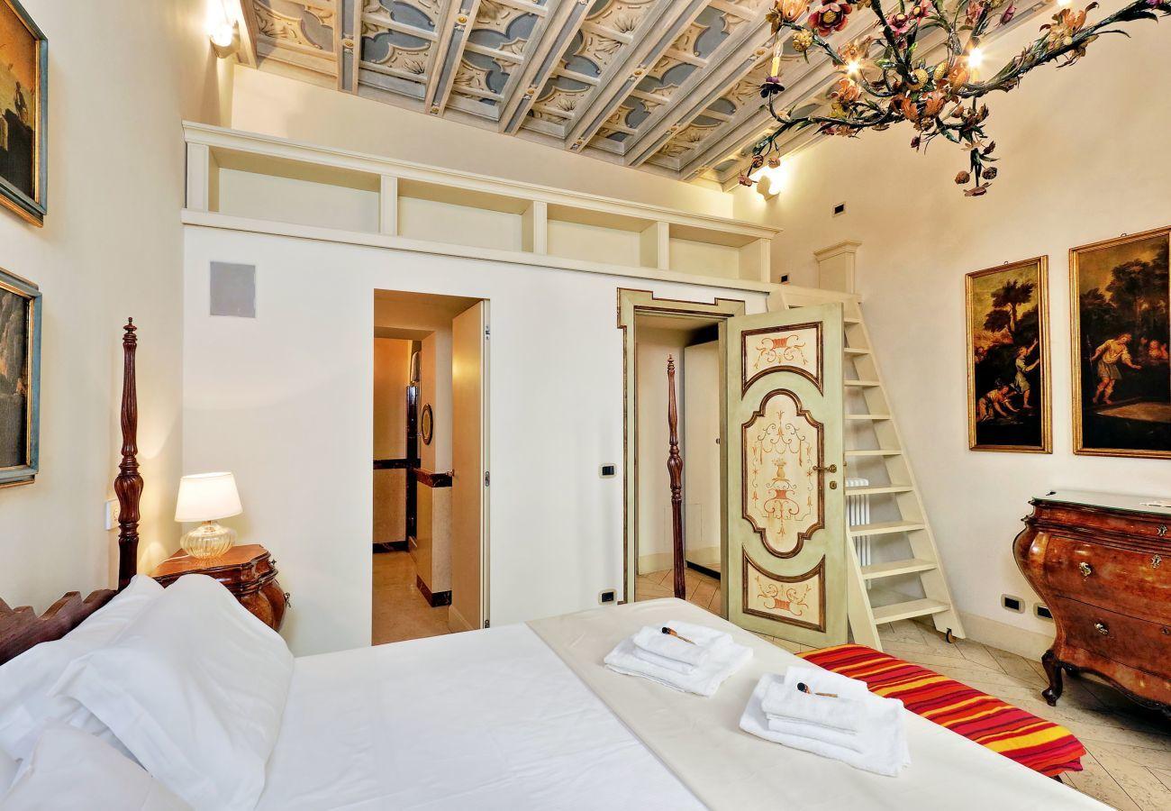 dormitorio con cama de matrimonio, mesitas de noche y tocador de estilo clásico y banco acolchado a los pies de la cama. Escalera