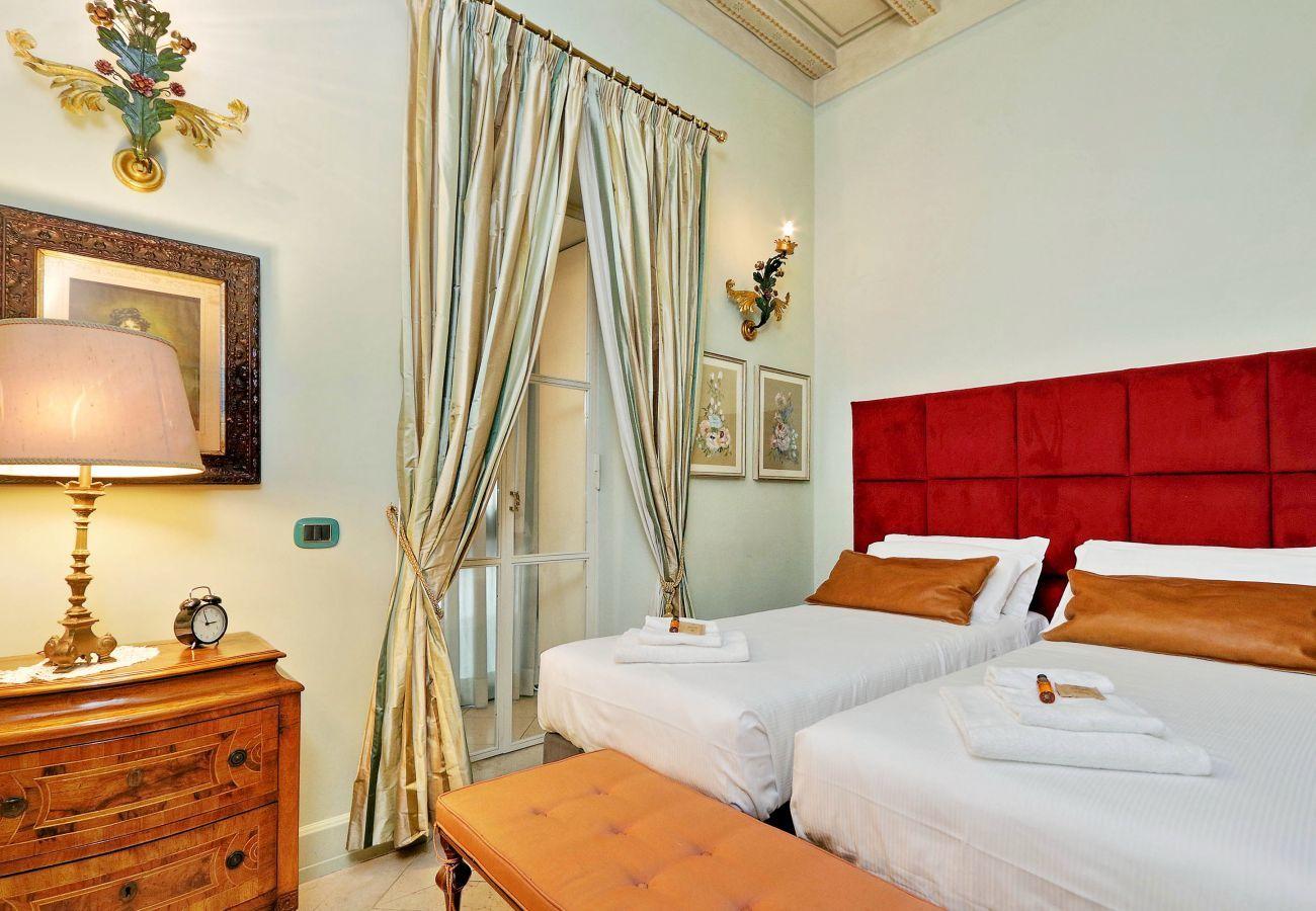 otro ángulo del dormitorio con dos camas individuales juntas y un banco tapizado a los pies. Estilo clásico
