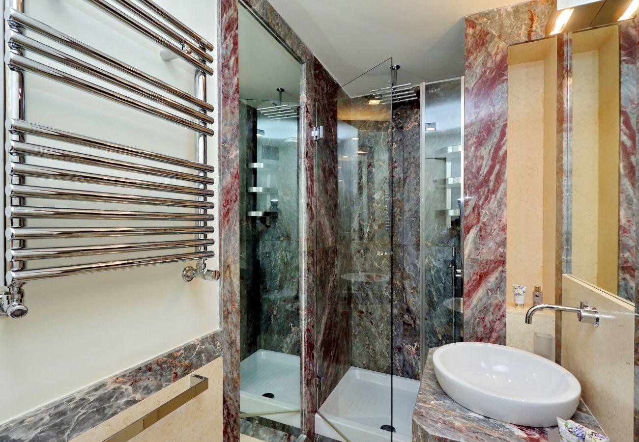 baño con ducha de vidrio, lavabo y acabados en mármol