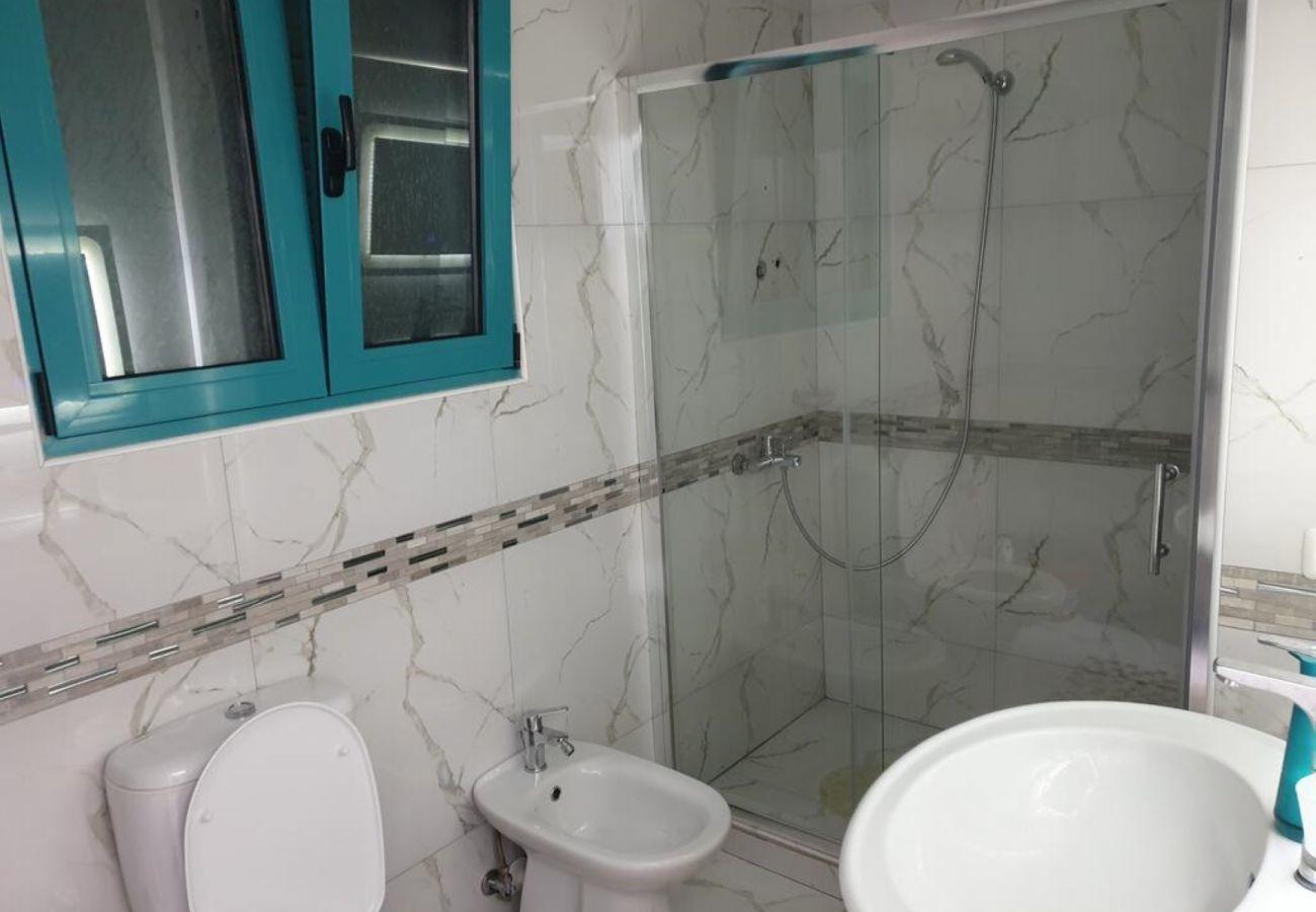 Baño equipado con lavabo, cabina de ducha y ventanas.