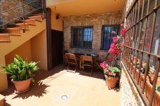 vu d'angle de la terrasse ensoleillée de l'appartement AMETLLER à Begur avec escaliers, table, chaises et plantes