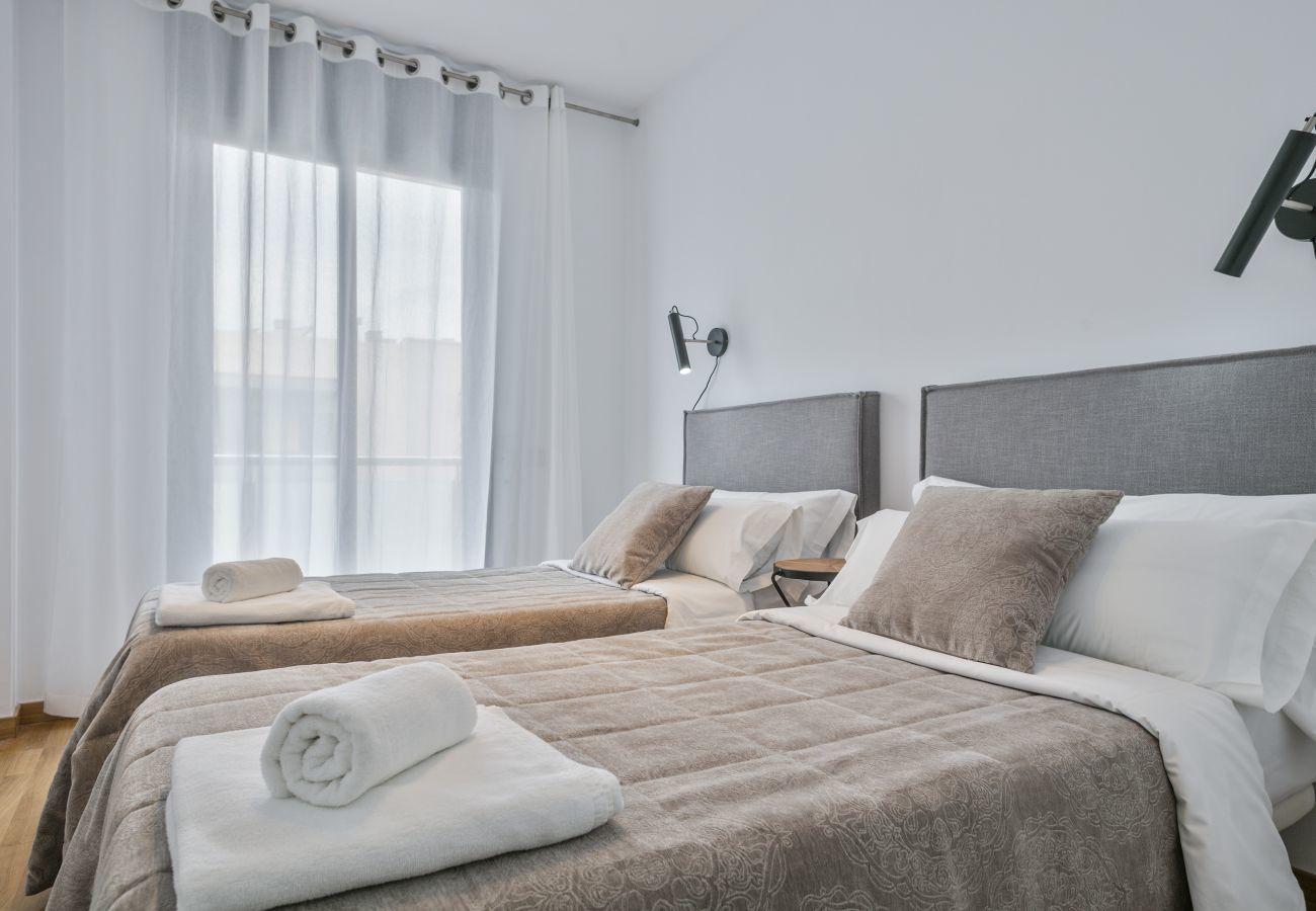 chambre principale avec salle de bain privée avec baignoire et placards dans un appartement supérieur à Barcelone