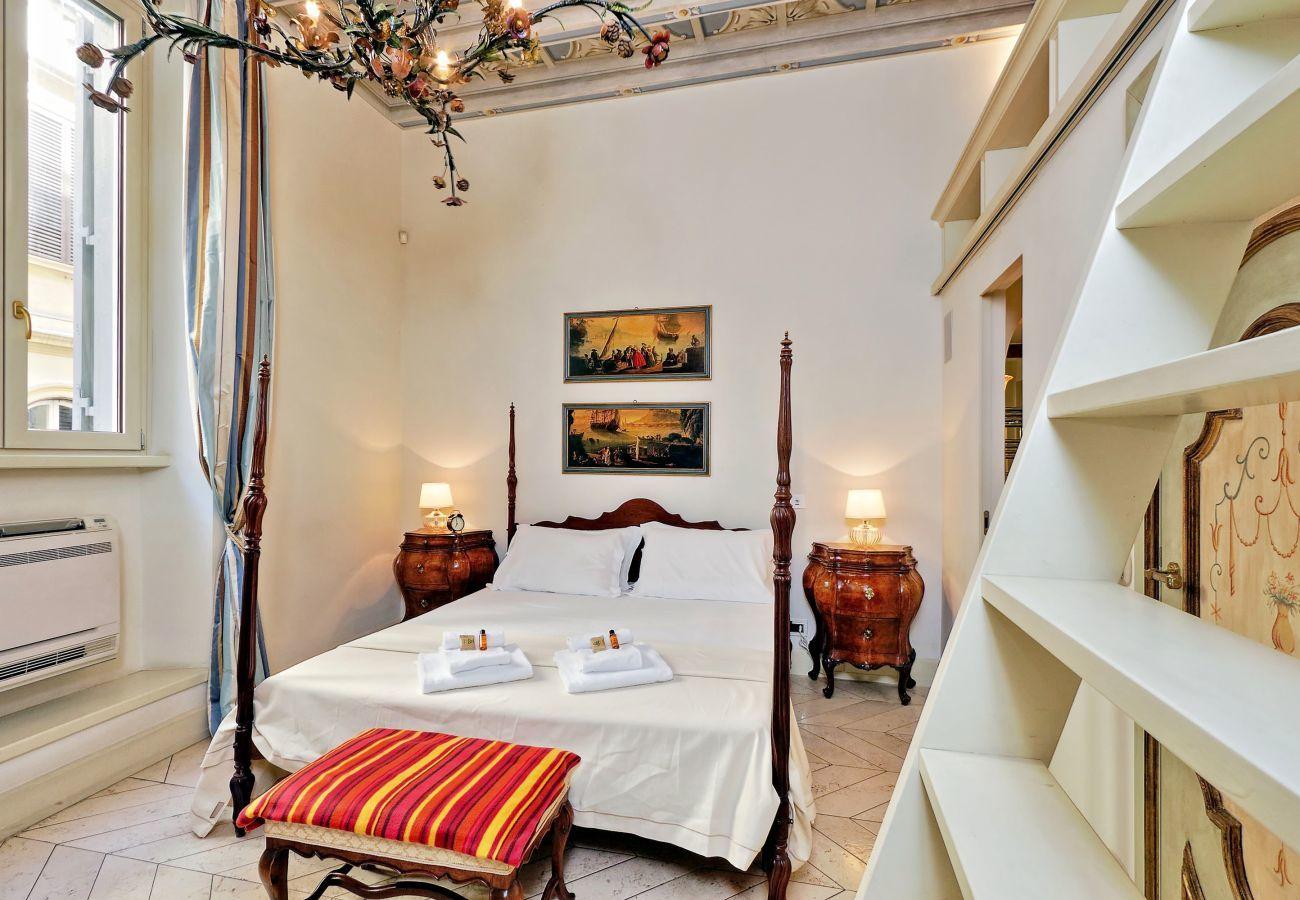 chambre avec lit double, tables de chevet de style classique et banc rembourré au pied du lit. Détail de l'escalier