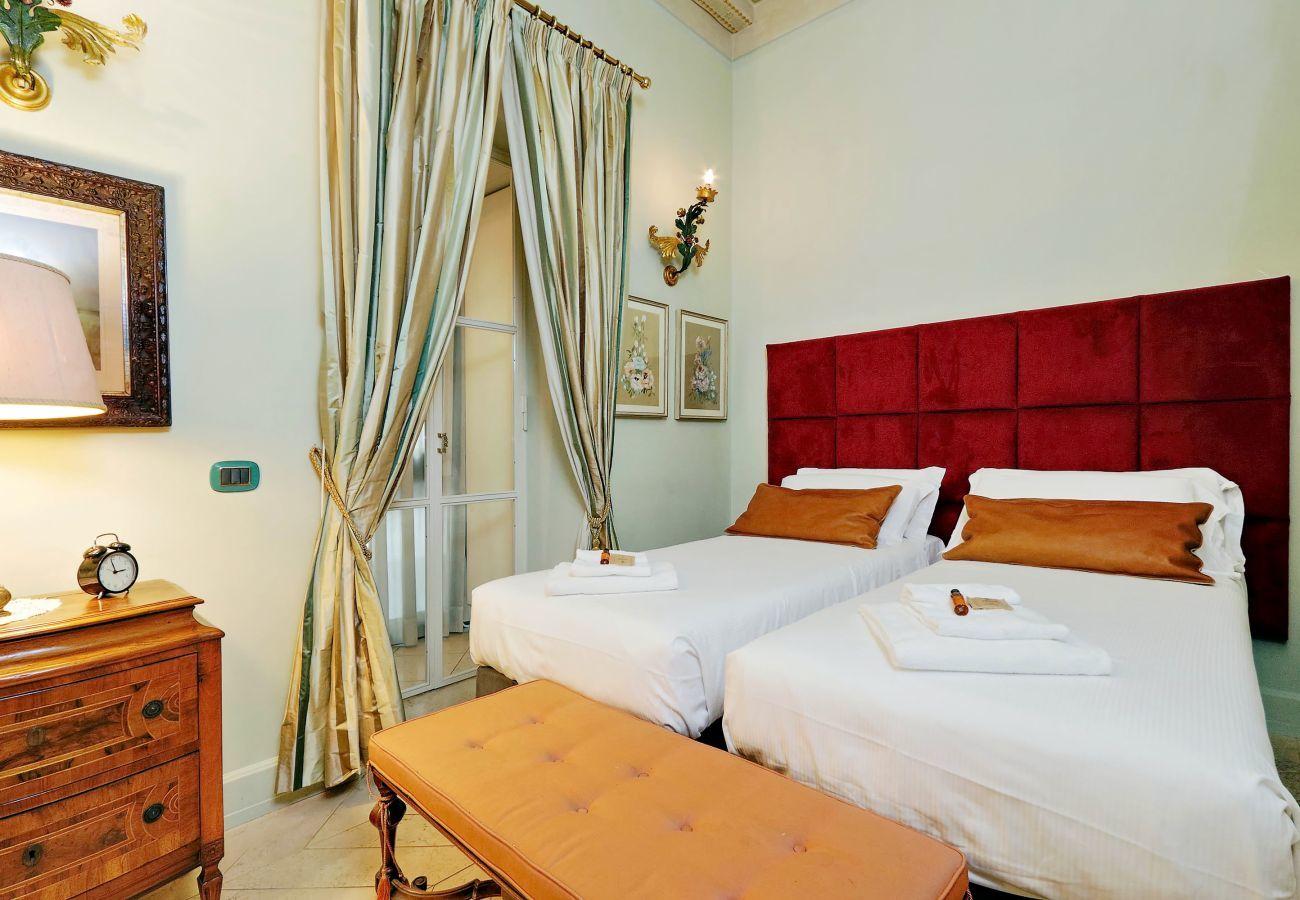un autre angle de la chambre avec deux lits simples rapprochés et un banc rembourré au pied. Style classique