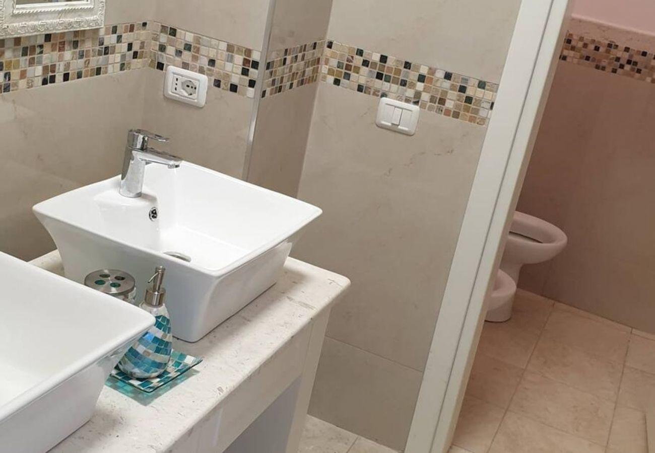 Salle de bain équipée de deux lavabos et entrée aux toilettes