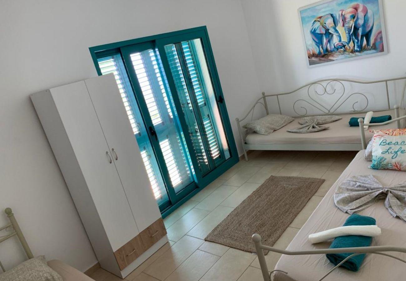 Chambre avec deux lits simples, fenêtres et placard
