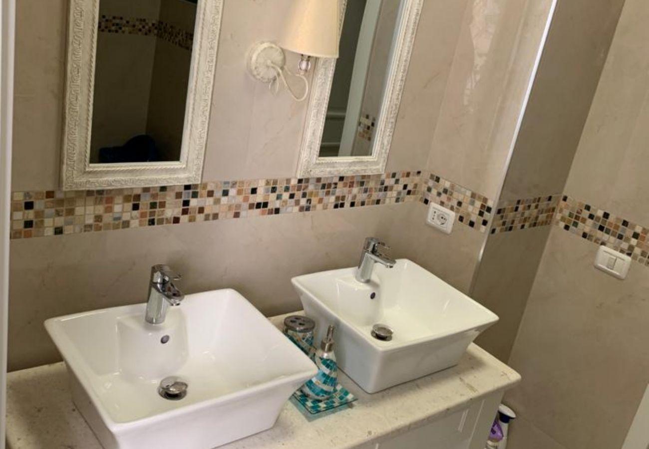 Salle de bain équipée de deux lavabos et de deux miroirs