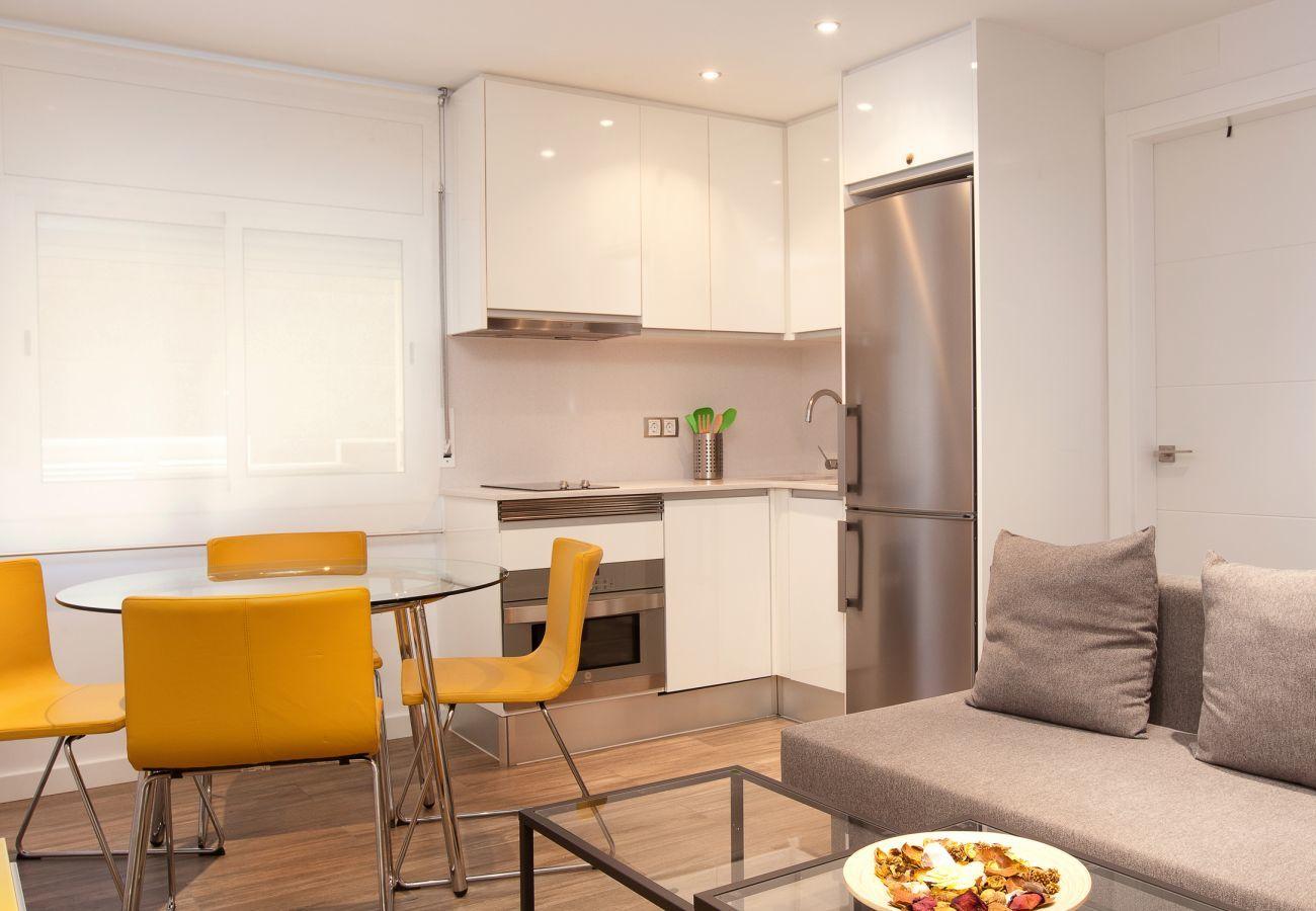 soggiorno e cucina di un appartamento con due camere da letto vicino alla Sagrada Familia e all'Ospedale La Pau