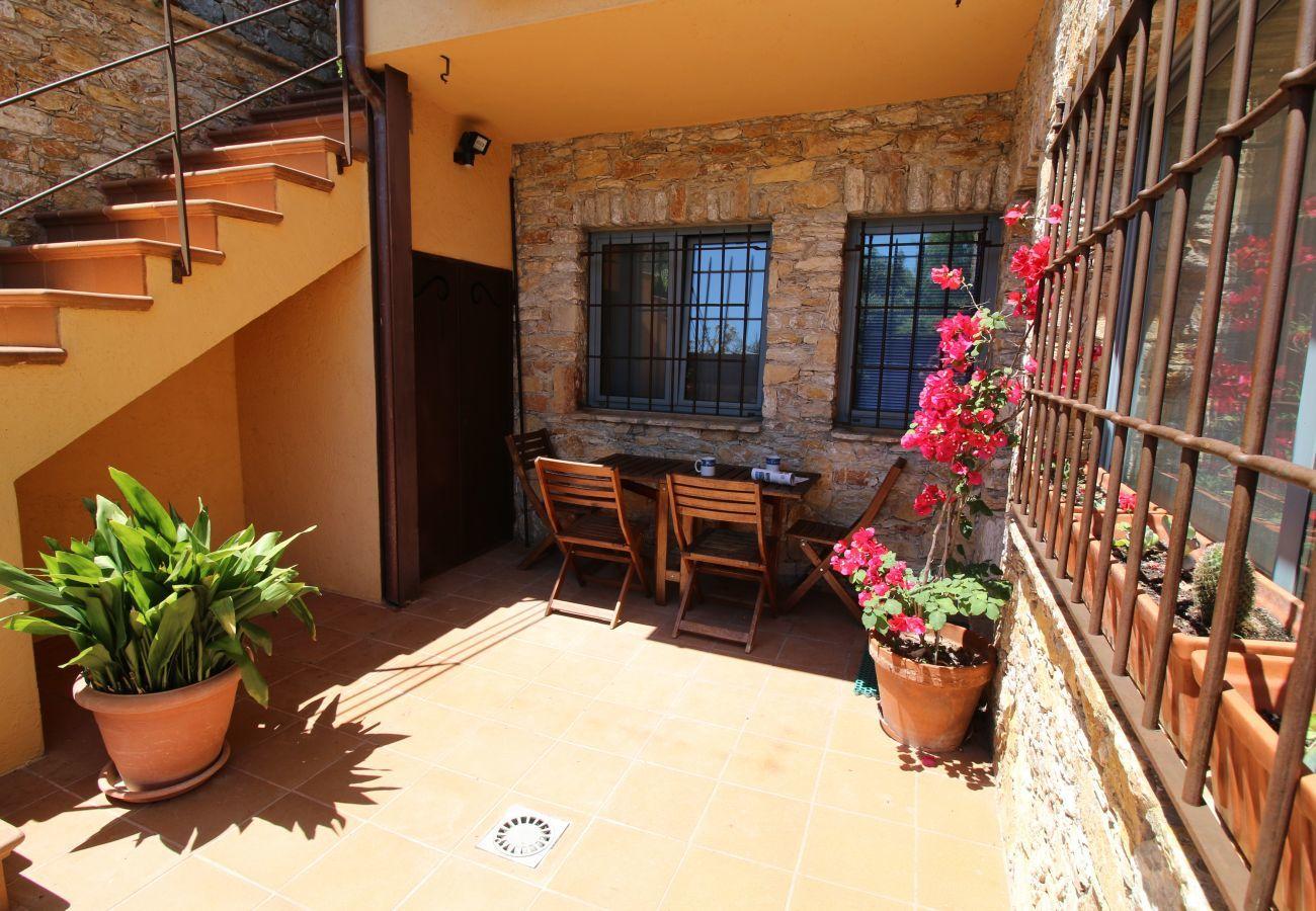 vista d'angolo della terrazza soleggiata dell'appartamento AMETLLER a Begur con rampa di scale, tavolo, sedie e piante