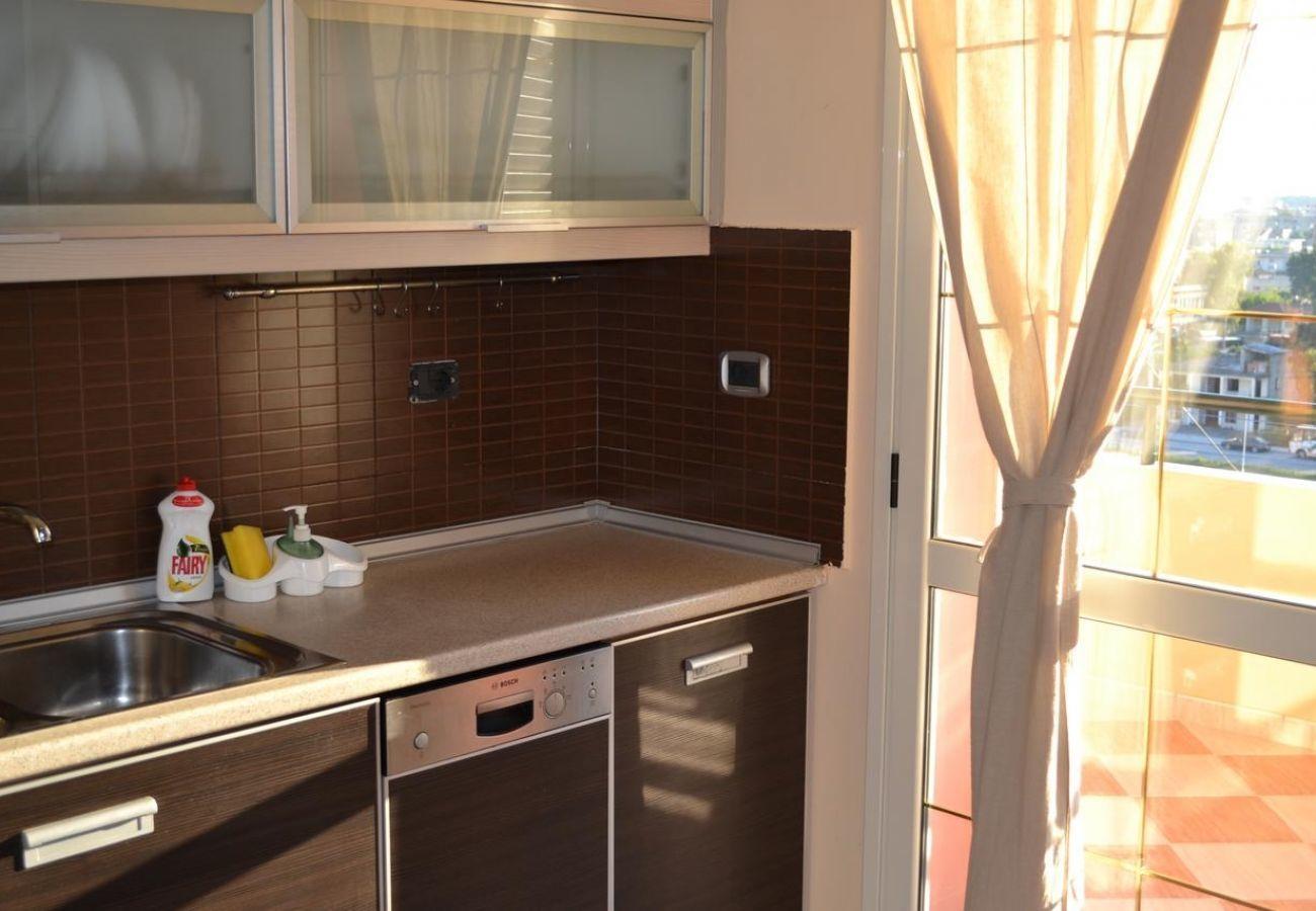Vista da una parte della cucina abbastanza ben arredata e dal balcone
