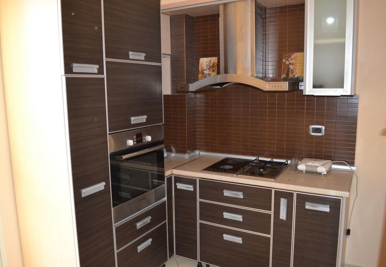 Cucina arredata con molti armadi, stufa in maiolica e microonde