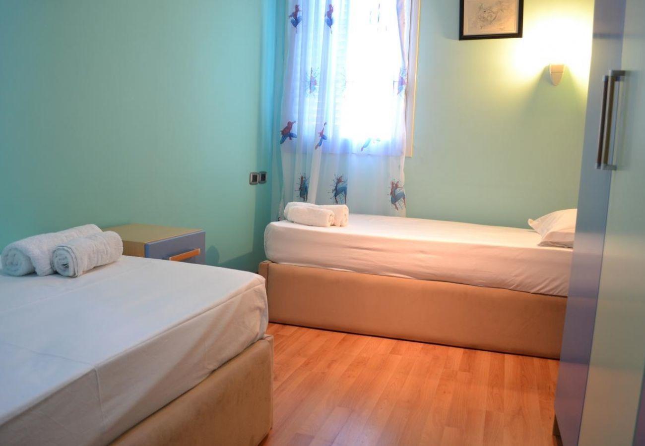 Camera da letto con due letti singoli e finestre coperte da bellissime tende