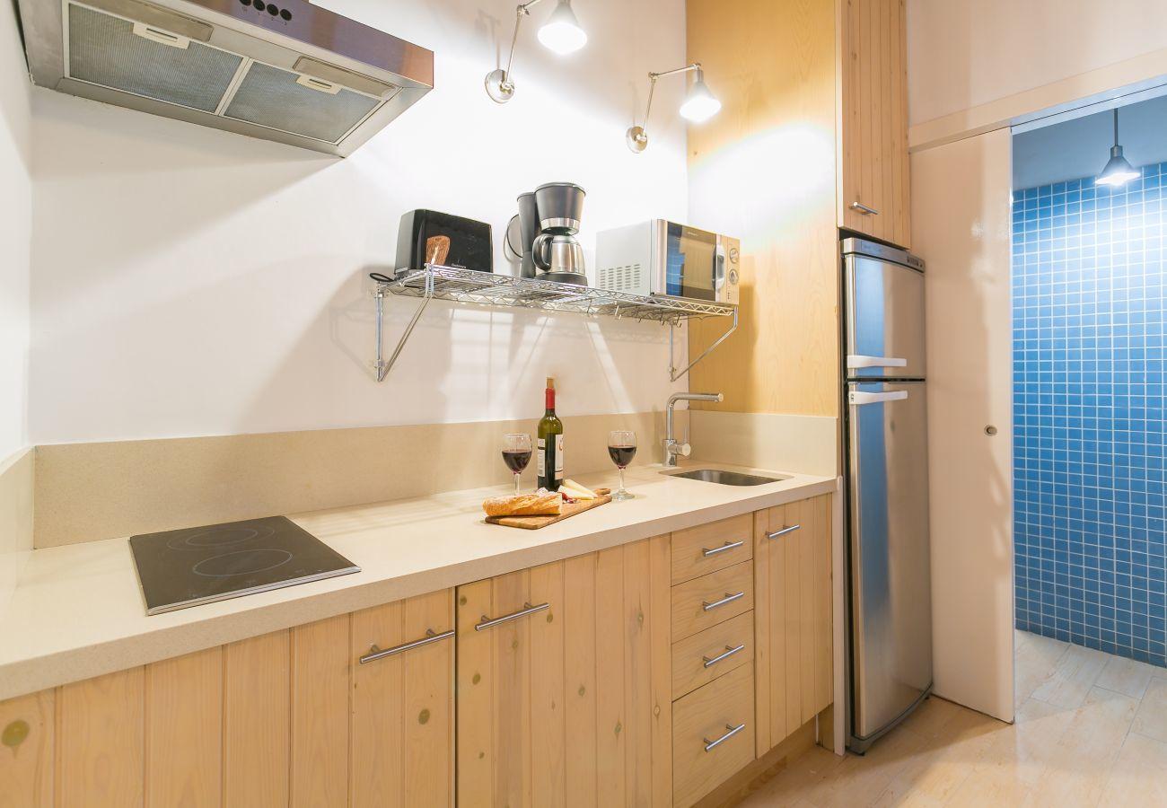 Cucina essenziale con piano cottura in vetroceramica in appartamento vicino alla spiaggia di Barceloneta