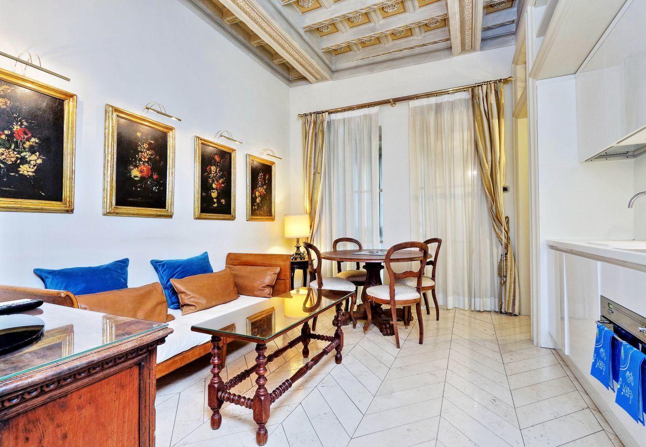 salone con vista completa di cucina, divano, tavolinetto e tavolo da pranzo