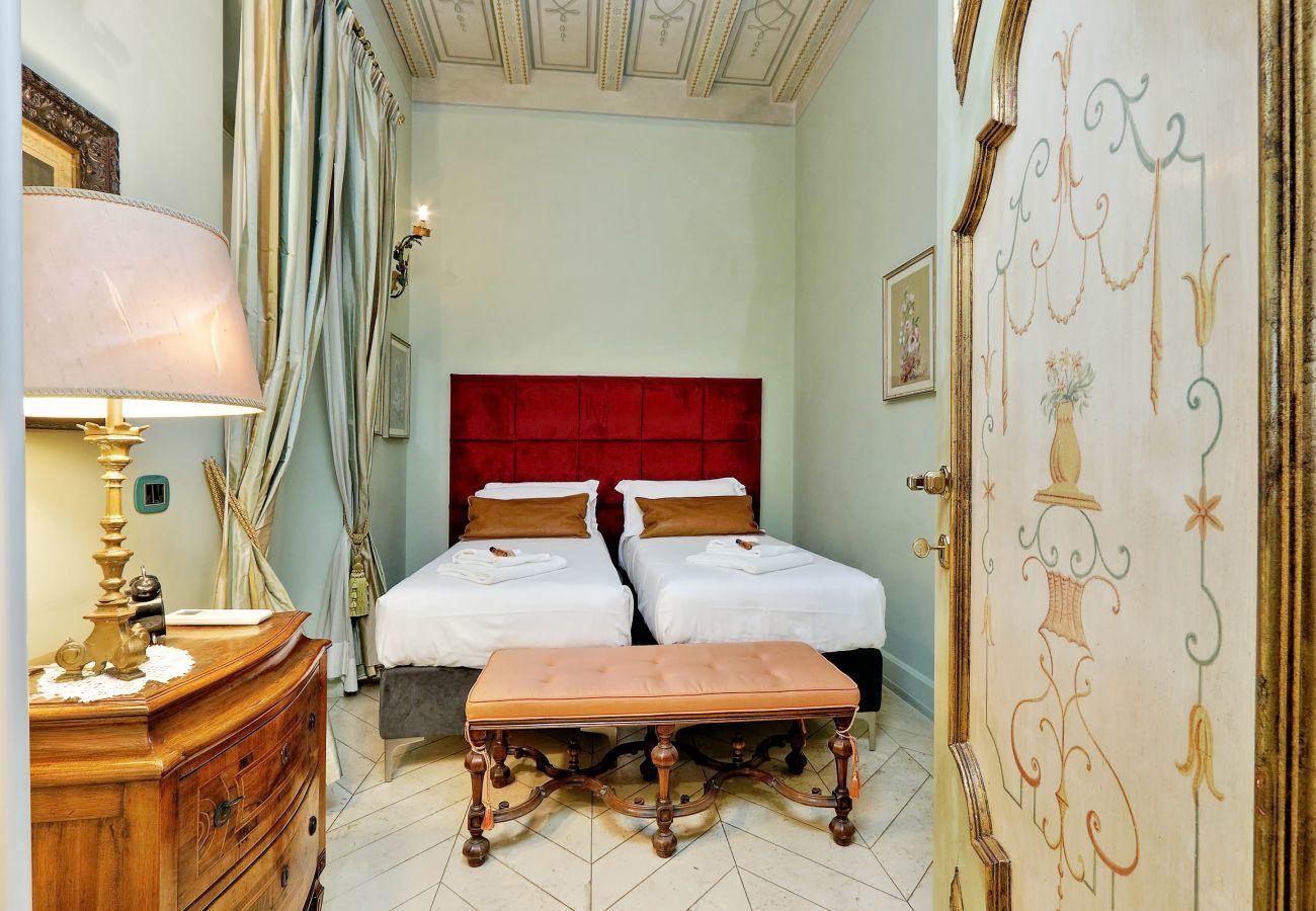 camera da letto in stile classico con due letti uniti, panca imbottita ai piedi dei letti