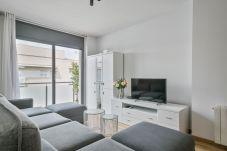 sala de estar bem iluminada com TV e saída para a varanda do apartamento de 3 quartos