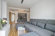sala de estar com TV, sofá confortável e copa em apartamento de 3 quartos