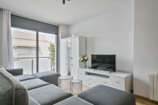 bright living room with TV and exit to the balcony in 3-bedroom apartment