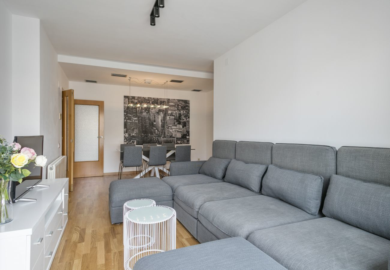 living room with TV, comfortable cauch and dining area in 3-bedroom apartment