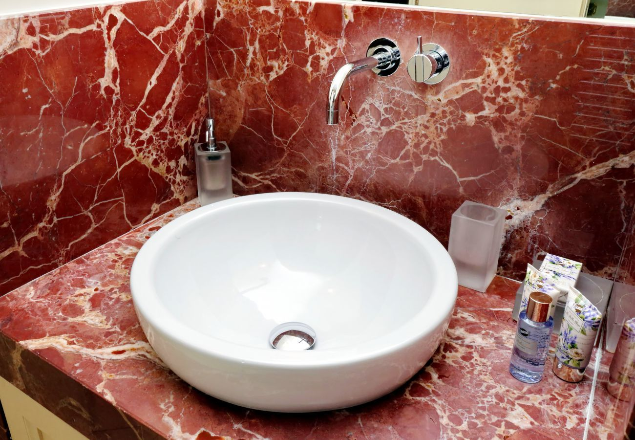 bathroom sink with marble base and various dispensers