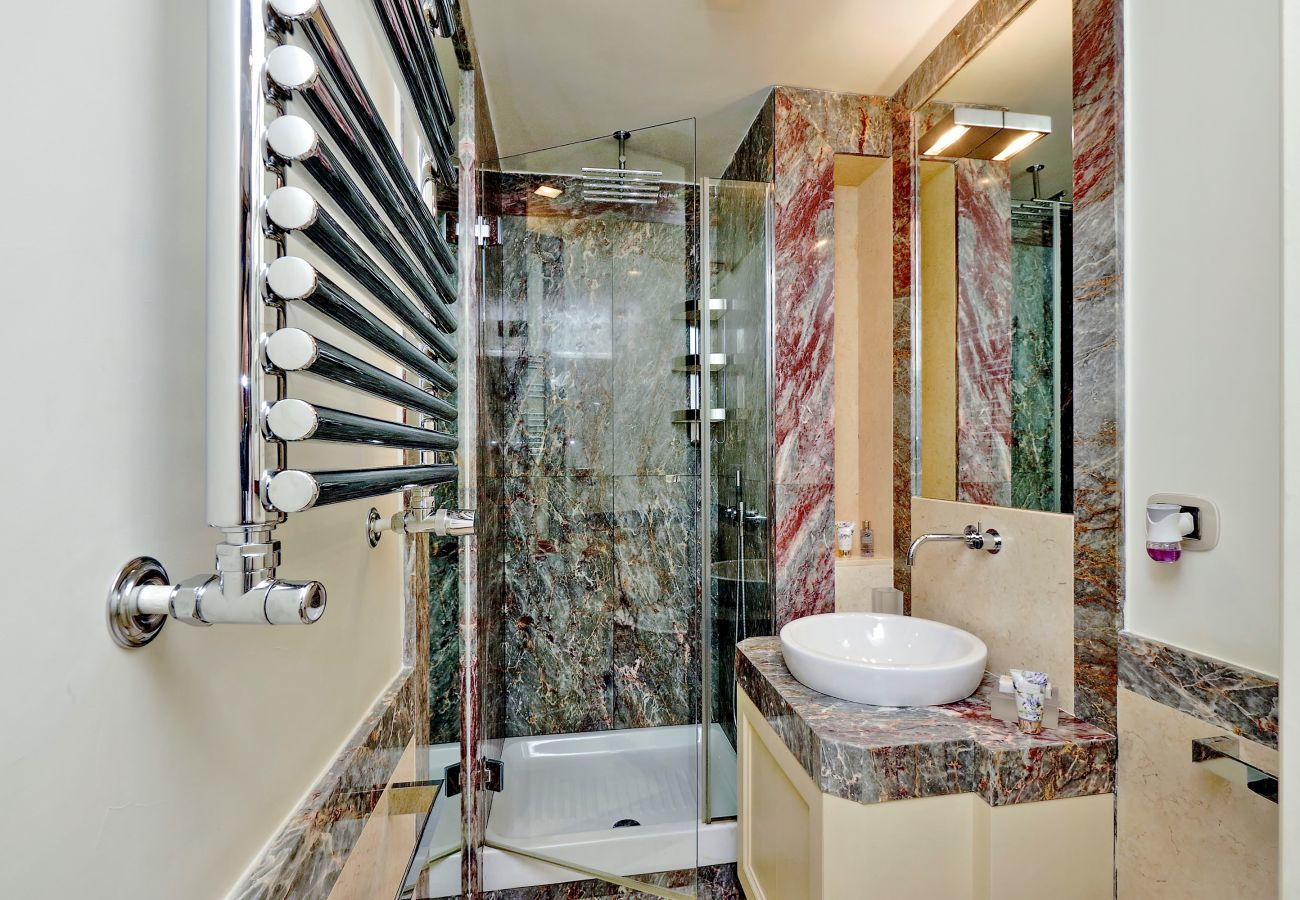 bathroom with glass shower, sink and marble finishes